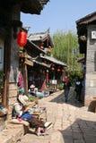 一个老妇人采取在丽江老镇鹅卵石街道上的休息  免版税库存图片
