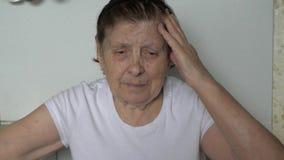 一个老妇人采取她移交她有头疼的头 影视素材