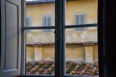 从一个老意大利窗口的看法与在一个铺磁砖的屋顶和墙壁的木快门有窗口的 免版税图库摄影