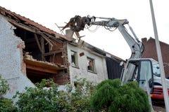 一个老房子拆毁与挖掘机 免版税库存图片