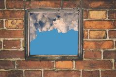 一个老房子的墙壁的片段有红砖和和看法砌的从小窗口与云彩天空 库存照片