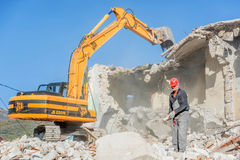 一个老房子的爆破有挖掘机的 库存图片