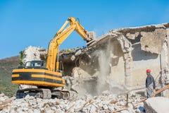 一个老房子的爆破有挖掘机的 库存照片