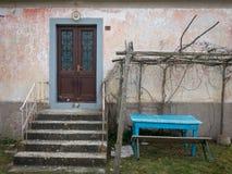 一个老房子的蓝色桌和入口有台阶的 免版税库存图片