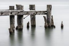 一个老打破的码头的末端,站立在镇静tra的岗位特写镜头  图库摄影