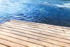 一个老木码头的角落有蓝色河的 库存图片