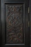 一个老木门的被雕刻的盘区 免版税库存照片