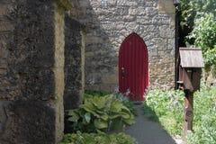 一个老石教会的大红色门 免版税库存照片