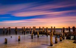 一个老码头的废墟在日落的在晚上靠岸,在开普梅,新 免版税图库摄影
