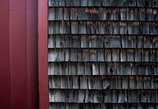 一个老磨房大厦的被风化的木瓦对红色木墙壁 免版税库存照片