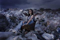 一个老篮子的一个女孩在垃圾堆 库存照片