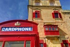 一个老红色磁卡电话摊在有一个老公寓的历史的城市瓦莱塔在背景中 免版税库存图片