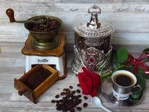 一个老经典磨咖啡器、银色咖啡瓶子、一杯咖啡和一朵红色玫瑰 减速火箭的样式 免版税库存照片