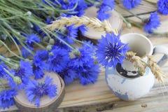 从一个老葡萄酒花瓶的构成有蓝色花的 免版税库存照片