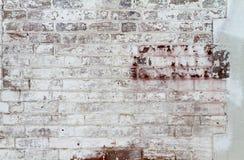 一个老被绘的砖墙 剥皮白色的油漆切削和 库存照片