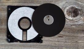 一个老计算机磁盘的里面零件在年迈的木头的 免版税图库摄影