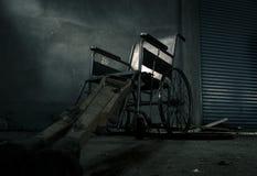 一个老轮椅和老木拐杖在老屋子里 老轮椅被抛弃了 这是偏僻和可怕概念 免版税库存照片
