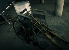 一个老轮椅和老木拐杖在老屋子里 库存照片