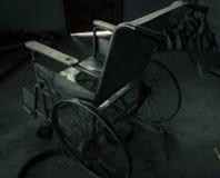 一个老轮椅在老屋子里 老轮椅被抛弃了 这是偏僻和可怕概念 免版税库存图片