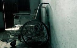 一个老轮椅在老屋子里 老轮椅被抛弃了 库存照片