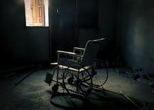 一个老轮椅在老屋子里 免版税库存照片