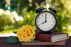 一个老闹钟、堆书和在一张木桌上的一朵玫瑰 书、一块手表和一朵玫瑰在绿色自然本底 复制s 库存图片
