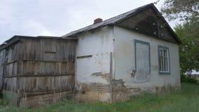 一个老,被放弃的房子在村庄,树背景的  在顿涅茨克附近的被放弃的房子 被毁坏的房子和 库存图片