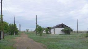 一个老,被放弃的房子在村庄,树背景的  在顿涅茨克附近的被放弃的房子 被毁坏的房子和 免版税库存照片