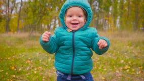 一个耳朵老孩子通过秋天公园跑并且微笑慢动作 常平架 股票录像