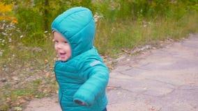 一个耳朵老男孩在秋天公园跑并且微笑慢动作 常平架 股票视频