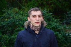 一个聪明的严肃的年轻人的画象有时髦的理发就座的反对自然绿色离开背景 英俊的深色的stude 库存照片