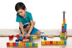 有玩具的聪明的小男孩在地板上 库存图片