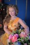 一个聪明的礼服桔子的女孩 免版税库存图片