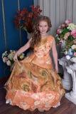 一个聪明的礼服桔子的女孩 免版税库存照片