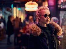 一个肉欲的女孩身分在街道上的夜 有启发性牌,氖,光 库存照片