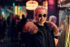 一个肉欲的女孩身分在街道上的夜 有启发性牌,氖,光 图库摄影