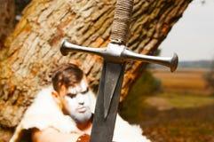 一个肌肉古老战士的画象 在前景的剑 免版税库存图片