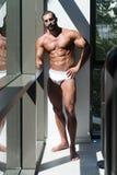 一个肌肉赤裸上身的男性的画象在内衣的 免版税库存照片