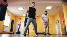 一个肥满人和亭亭玉立的女孩有个人教练的在健身房 在拳击的火车打击 健康和健身 锻炼和实践 影视素材
