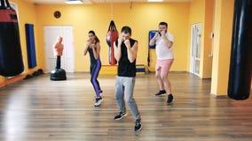 一个肥满人和亭亭玉立的女孩有个人教练的在健身房 在拳击的火车打击 健康和健身 锻炼和实践 股票录像