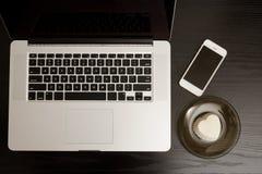 一个膝上型计算机键盘、智能手机和点心的顶视图在一张黑木桌上 免版税库存照片