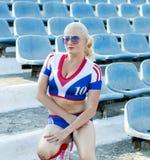 一个膝盖的美丽的女运动员在体育场停留演出地  库存照片