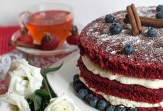 一个自创蛋糕和一杯玻璃茶用精美乳脂状的花、蓝莓、臀部和桂香装饰的鞋带表面上的 免版税图库摄影