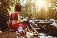 一个自由职业者行家女孩的一张被定调子的画象有玻璃和一个时髦的盖帽的在有膝上型计算机下跪的一条毯子穿戴了 免版税库存照片