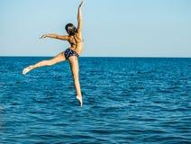 一个自由飞行飞跃的女孩到海里 库存图片