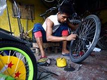 一个自行车修理人在自行车商店固定轮胎 图库摄影