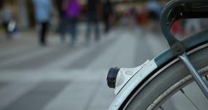 一个自行车轮子的特写镜头有走在购物街道上的人的在背景中 股票录像