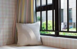 一个舒适靠窗座位的休息区与坐垫的早晨 库存照片
