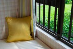 一个舒适靠窗座位的休息区与金坐垫的在水平的早晨 库存照片