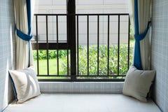 一个舒适靠窗座位的休息区与绿色坐垫的在水平的早晨 库存图片